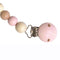 This pacifier holder is made of wooden beads. Some beads have a raw wood finish and some are painted pink or light neutral colours such as grey or beige. The technique of painting ensures absolute safety for your baby. A stunning yet practical product.