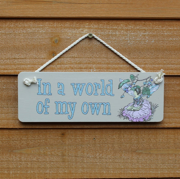"Painted wooden board with motif ""In a world of my own"" and a picture of a fairy, comes with a string for hanging from the door."