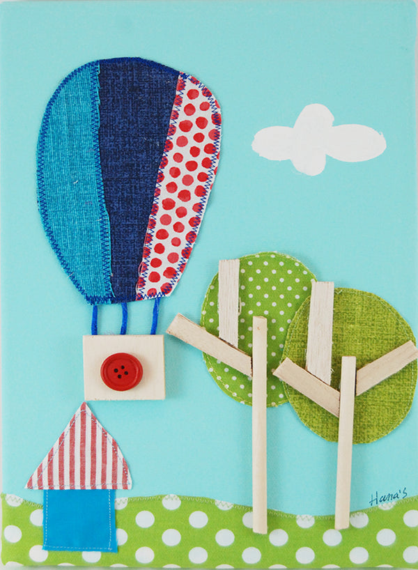 Picture of a hot air balloon on a painted canvas with layered fabrics to provide a three-dimensional effect.