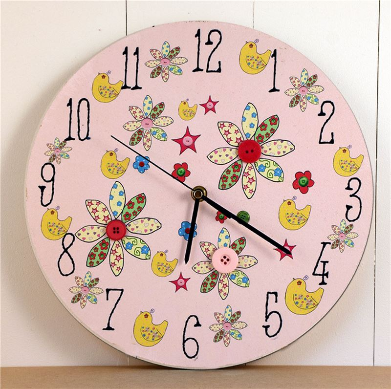 A pretty pink painted clock with pictures of flowers, birds and real buttons. Matching designs are available on other products on Rooms for Rascals.