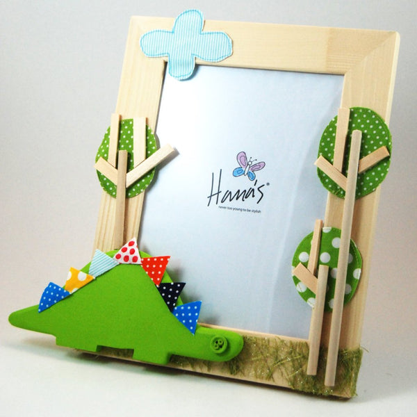 Natural wood photo frame with a dinosaur theme. The dinosaur, trees and cloud detail is attained through an array of layered fabrics and painted wood giving a three-dimensional effect.