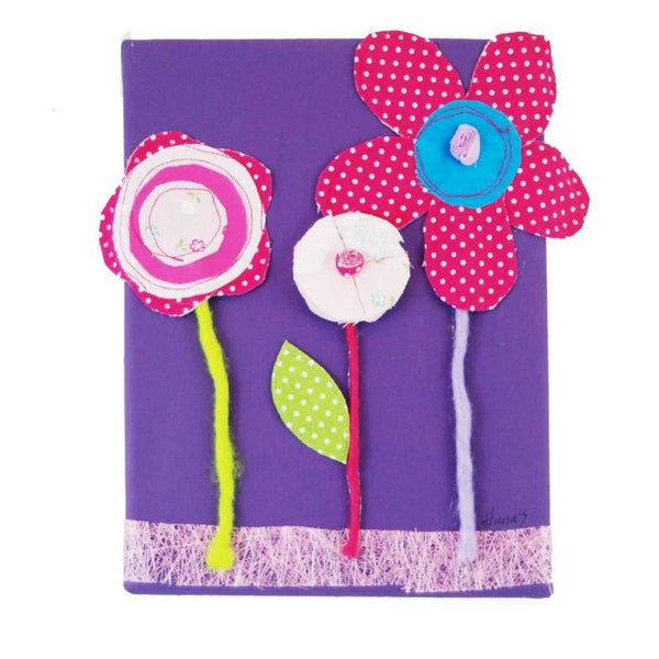 Picture of flowers on a purple painted canvas with layered fabrics to provide a three-dimensional effect.