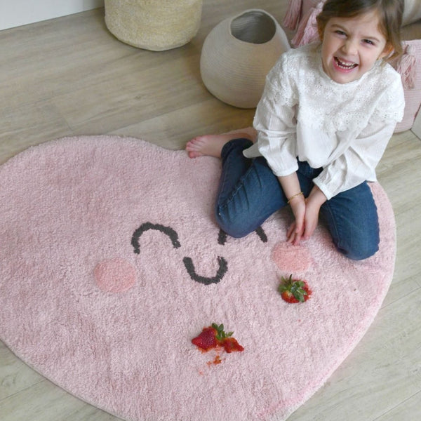 Spread love and kindness on this heart shaped rug from Lorena Canals. This soft, pink, smiling heart reminds us of childhood's unconditional love. With this beautiful rug, you can decorate your children's room with a modern and elegant style!