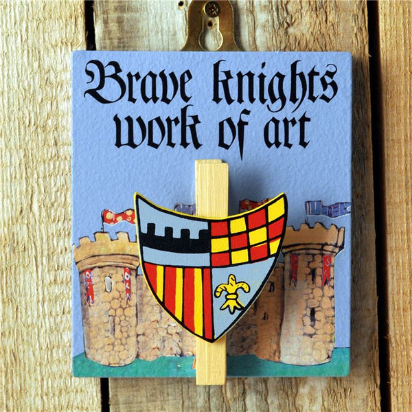 "Blue painted wooden base with a knight's shield peg and the message ""Brave knights work of art"". Complete with a hook for hanging on the wall."