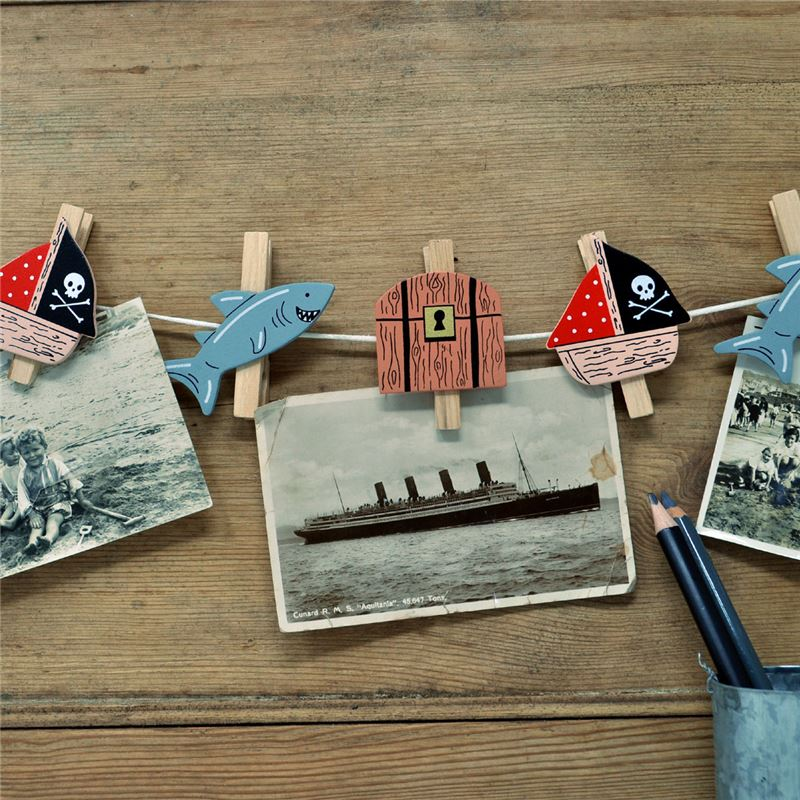 Wooden pirate ship, shark and treasure pegs on string with photos attached.