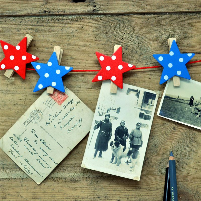 Wooden red and blue star-shaped pegs on string with photos attached.
