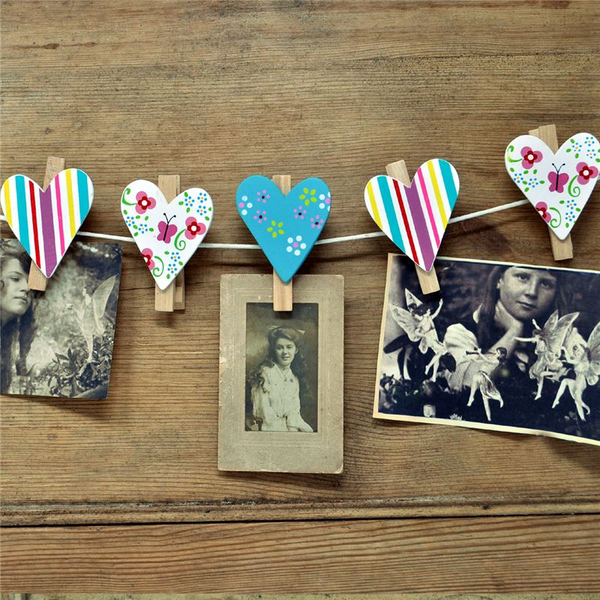 Beautiful and colourful wooden heart-shaped pegs on string with photos attached.