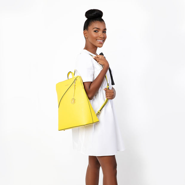 eila cherie leather yellow backpack alice, in the color sunshine. Worn by woman with high bun.