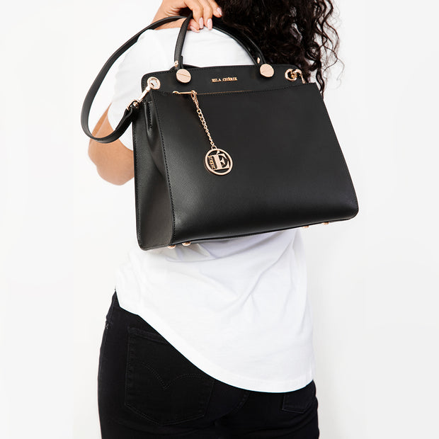 Close up view of Eila Chérie Onyx Black Leather Handbag held by woman wearing a white T Shirt