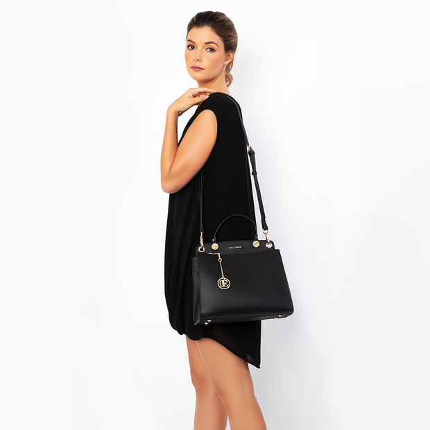 Eila Chérie Onyx Black Leather Handbag on the shoulder of a woman wearing a black dress