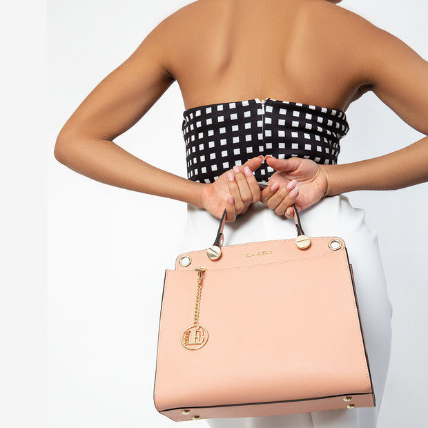 eila cherie leather audrey style handbag in the color peach held by model