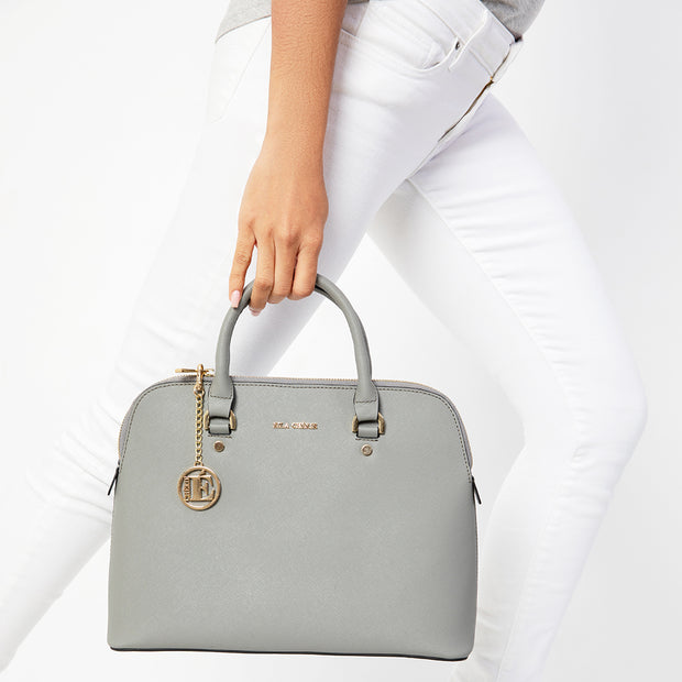 Eila Chérie Ash Grey Barbara Handbag held by woman in white jeans
