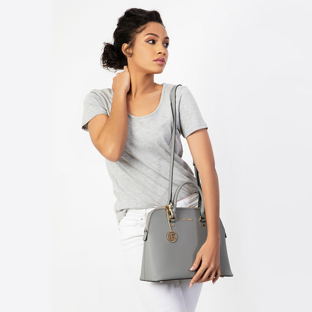 Eila Chérie Grey Barbara Handbag worn by woman in white jeans