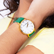 Eila Chérie Marble womens watch Olivia with kelly green colored leather strap on the wrist of a woman in a yellow dress