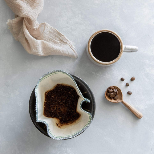 Organic coffee filter with grounds, bamboo spoon with coffee beans, and coffee cup