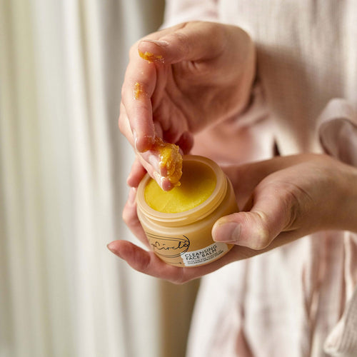 Person holding a jar of the yellow cleansing face balm in one hand, scooping out a quarter sized amount onto fingers with the other hand.