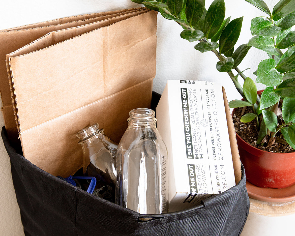 A reusable recycling bag filled with cardboard, two glass bottles, and a Zero Waste Store taped packaging box