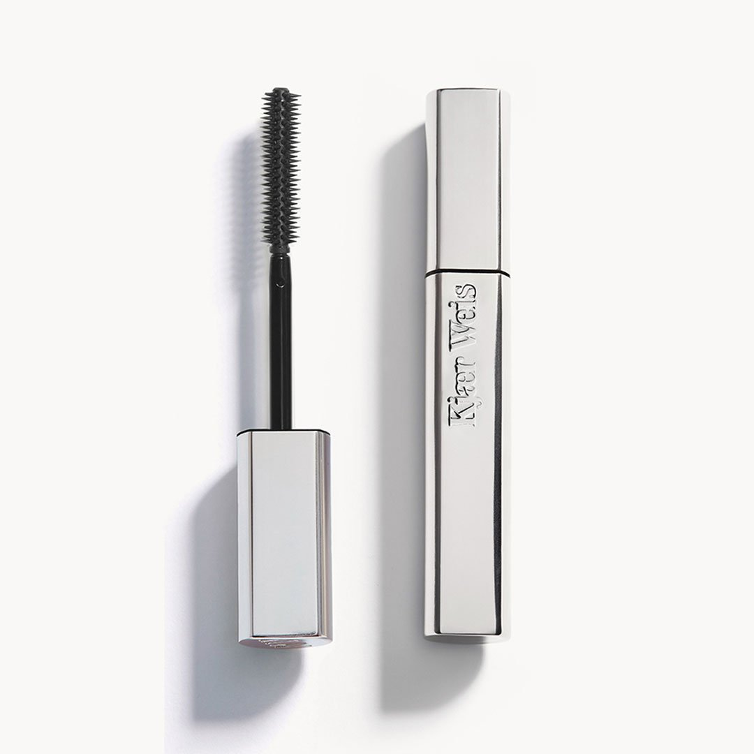 Closed metal mascara tube on the right, upside down wand on the left. Tube has Kjaer Weis embedded