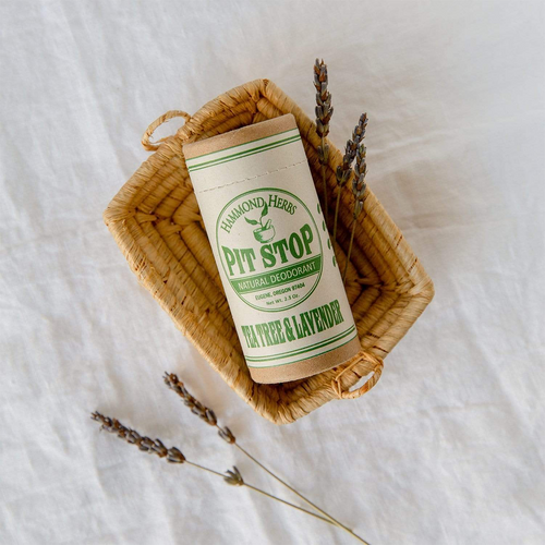 Cardboard tube resting in a wicker basket with herbs. Tube is labeled Pit Stop Natural Deodorant. Tea Tree & Lavender