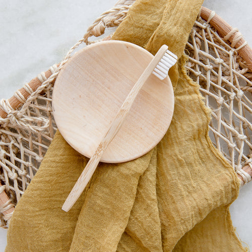 A bamboo toothbrush resting on a small circular bamboo dish and an arrangement of a mustard cloth and natural woven object