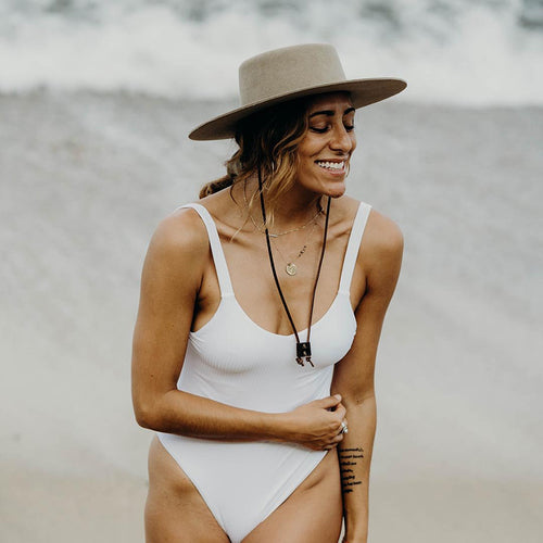 Woman in white one piece bathing suit with taupe flat rimmed boiler hat and long leather strap.