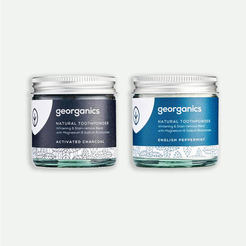 Two glass jars of georganics natural toothpowder in Activated Charcoal and English Peppermint flavors
