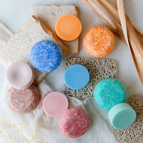 A collection of orange, blue, tan, pink, and turquoise shampoo and conditioner bars arranged on soap lifts, white muslin cloth, and small slabs of stone