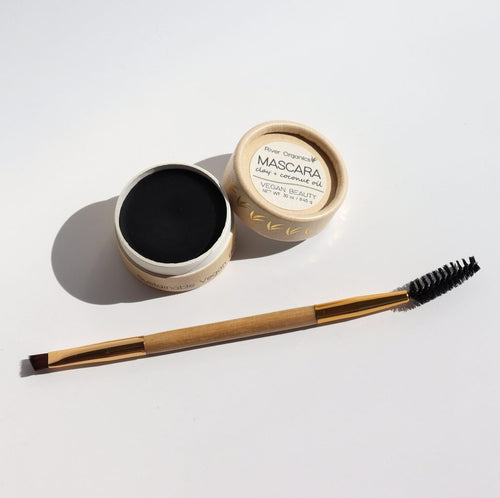 Small cardboard circle container containing solid black mascara. Life off to the side reads: River Organics Mascara. Mascara spoolie and eye shadow applicator combo brush sits in front