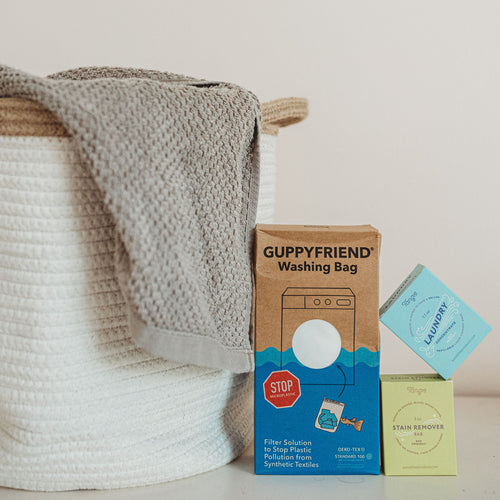 A boxed Guppyfriend Washing Bag, a boxed stain remover bag, and a boxed laundry concetrate next to a cloth laundry hamper with a gray towel hanging over the side