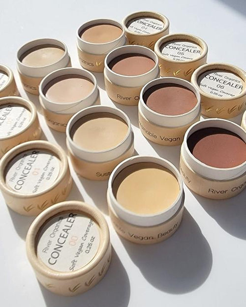 8 containers of River Organics concealers lined up in two rows with their lids on either side