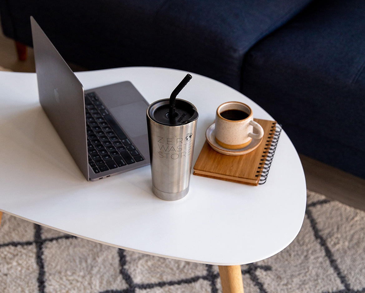 A laptop, a reusable stainless steel tumbler with a silicone straw cap, a small ceramic coffee cup and saucer, and a bamboo cover notebook on a white kidney-shaped coffee table