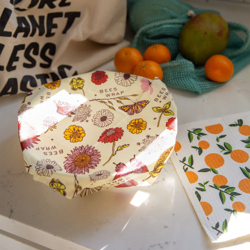 a bowl wrapped with flower print bees wrap, an orange print sponge cloth, and in the background a blue net bag of fruits