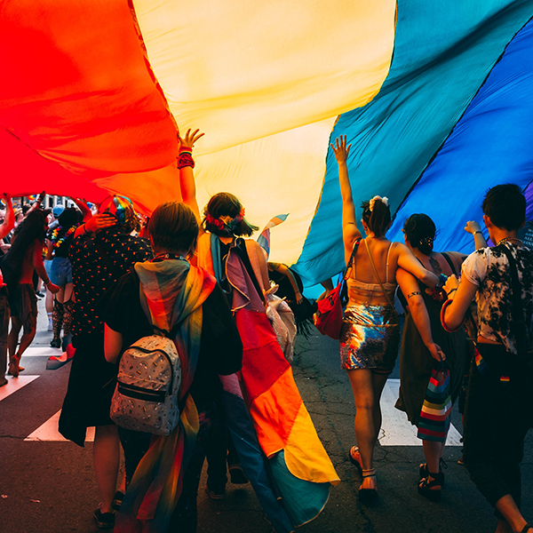 A group of young people under a large rainbow flag during Pride