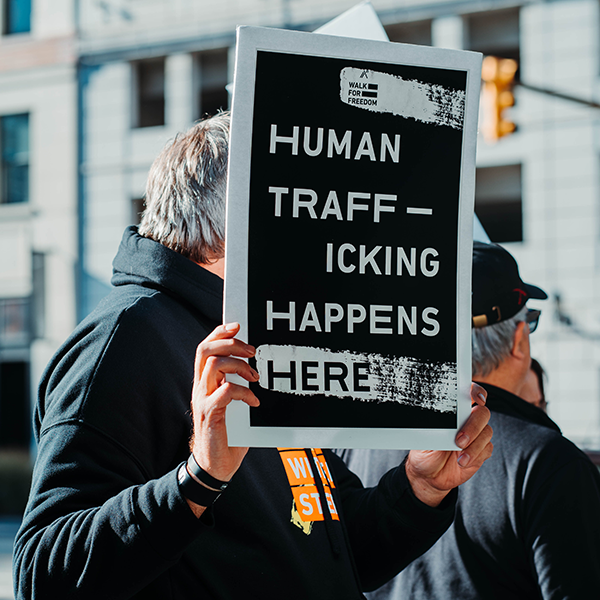 A man holding a sign in protest of human trafficking