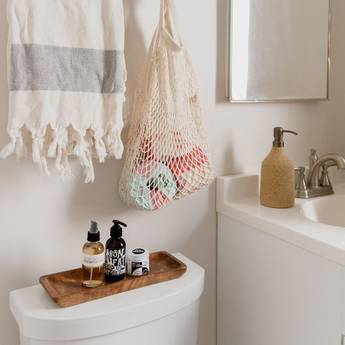 A white bathroom interior with a tasseled towel and netted bag holding toilet paper hanging on the wall, a wooden tray of skin care products placed on top of the toilet, and to the right a ceramic soap dispenser next to a sink