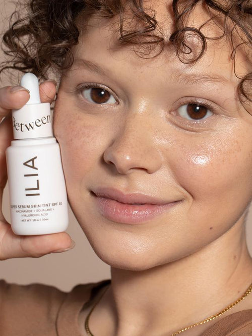 Woman wearing light, sheer coverage using Ilia Serum Foundation, faint but visible freckles showing.