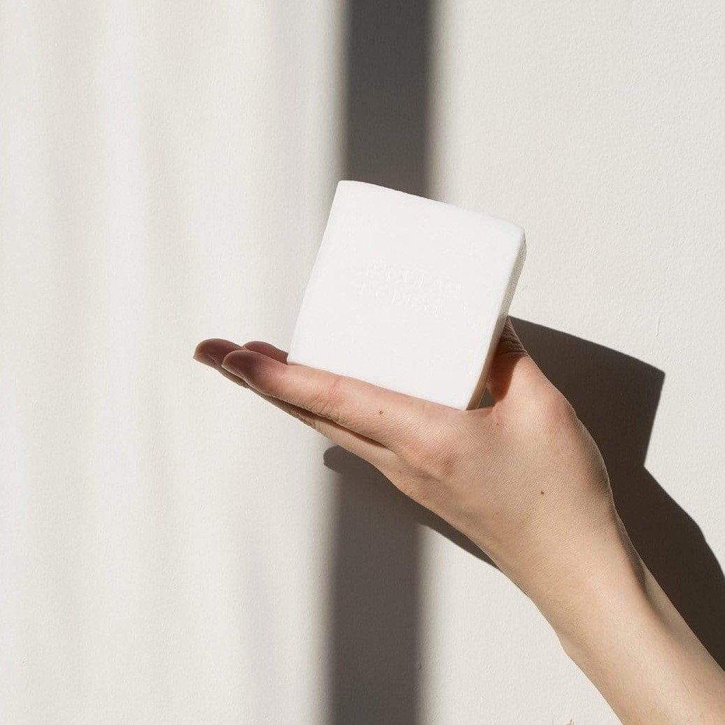 A hand holding a white cube of dish soap