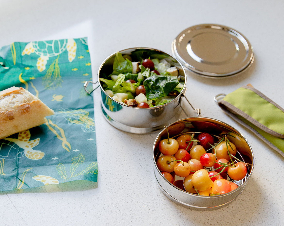 Two round stainless steel lunch boxes filled with salad and Rainier cherries. To the left is part of a baguette on a wax wrap, and on the right is a green utensil sleeve