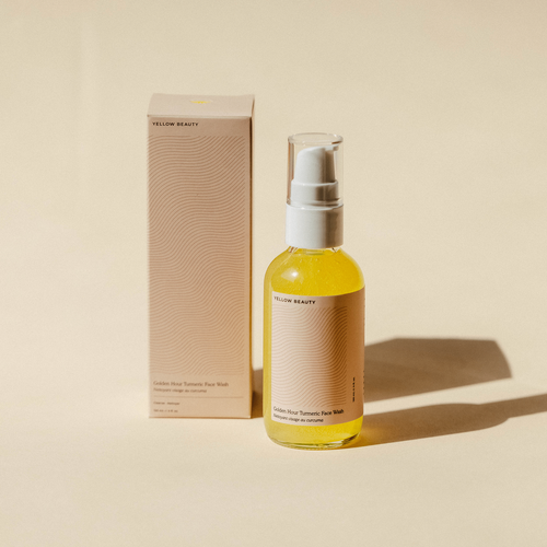Glass jar with brown plain label and white pump next to cardboard box. Face wash inside bottle is a light golden/yellow color