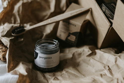 black and white glass jar and bamboo toothbrush on crumpled recycled paper