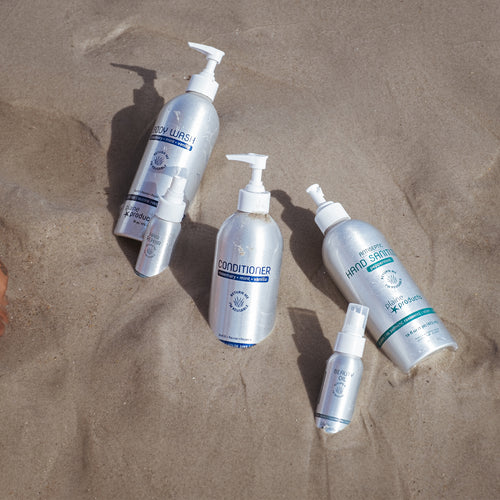 Metal bottles of hair and body care products partially buried in sand