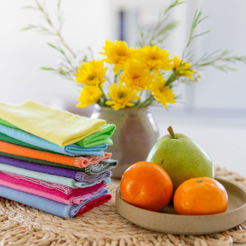Stacked rainbow cloth towels and a ceramic plate of fruits on a raffia woven mat, a vase of yellow flowers in the background