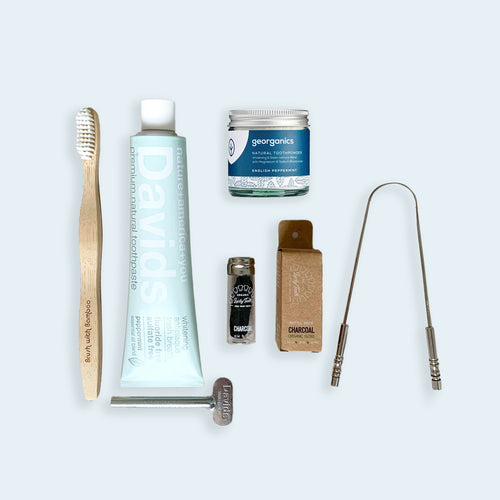 From left to right bamboo toothbrush, david's toothpaste tube with tube key underneath it, georganics tooth powder jar, bamboo charcoal floss in glass reusable jar, bamboo charcoal floss refill in cardboard box, and stainless steel tongue scraper