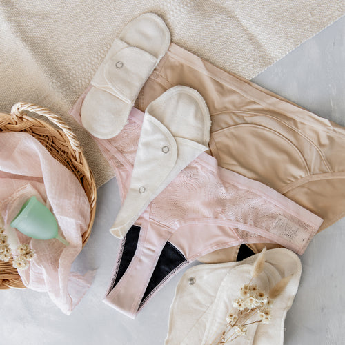 A selection of menstrual cloth pads and pantyliners, a mint-colored menstrual cup, and pink and nude menstrual underwear on a white surface.