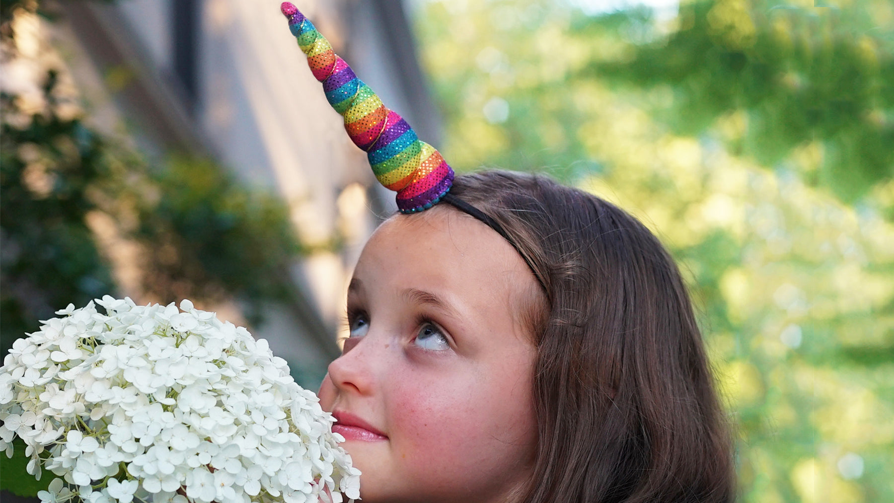 Little girl wearing unicorn horn near hydrangea flowers