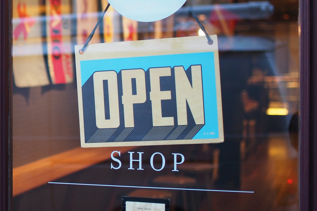 """""""Open"""" sign on glass entrance door of a business"""