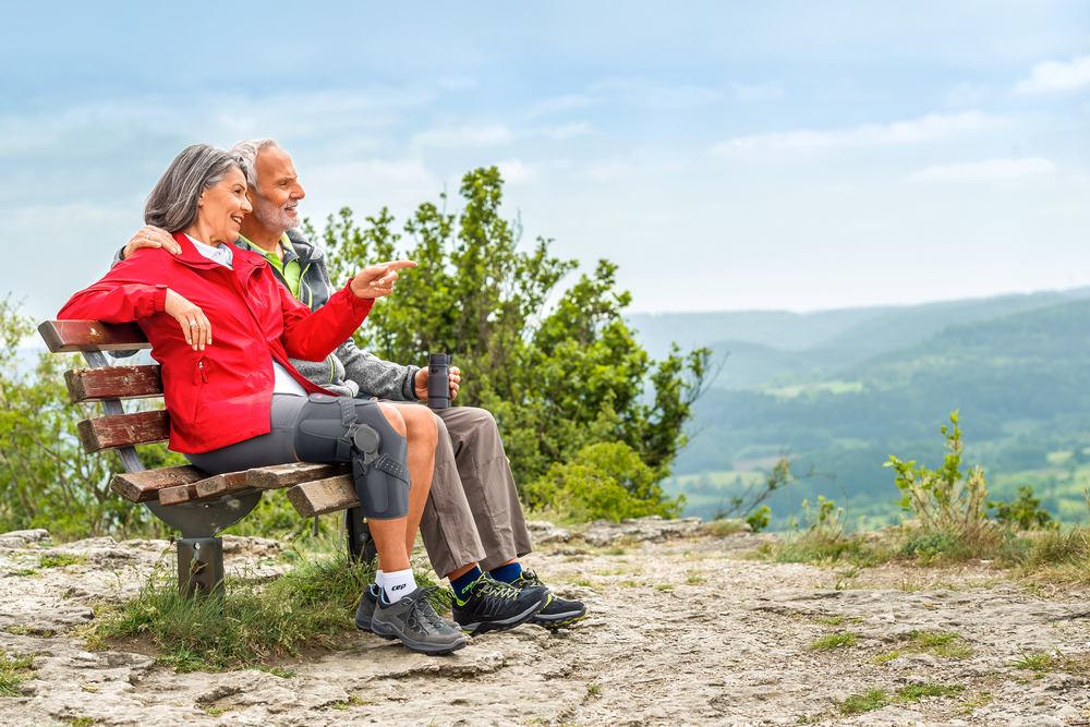 Two older people resting on bench during hike