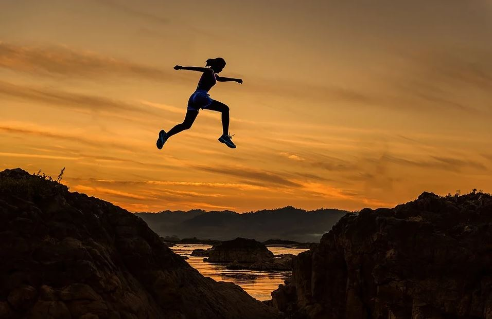 woman leaping over gap at dusk