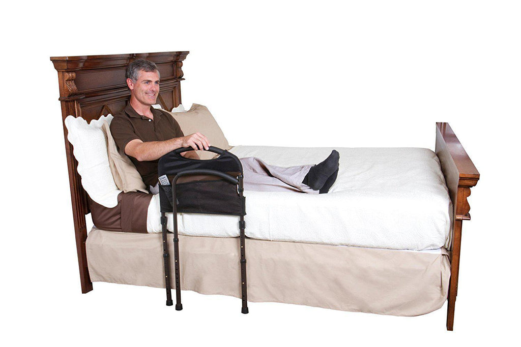 Man sitting in a bed holding onto a Stander Mobility Bed Rail