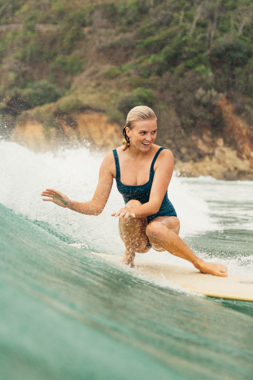 woman crouched down surfing wearing one piece surf swimsuit in bottle green